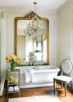 golden large wall mirror and white tub with yellow flowers in modern bathroom