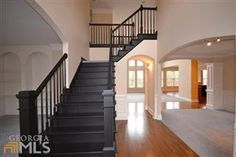 Love the black staircase in the entryway of a home
