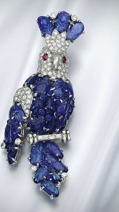 Sapphire, Ruby and Diamond Brooch, CARTIER, 1960s. Estimate £20,000–30,000.   Modelled as a cockatoo, the body set with carved  Sapphires and brilliant-cut  Diamonds and accented with  blue enamel, the eyes set with  oval Rubies, resting on a perch  set with baguette Diamonds,  signed Cartier, numbered,  French assay and maker's   marks, fitted case  stamped Cartier.  • •Note: Accompanied by a facsimile of the original purchase invoice form Cartier Monte Carlo, dated 24th March 1960.