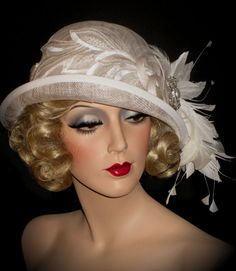 The ABBEYS WHITE CLOCHE design... The perfect selection for a day at the Derby, Gatsby Gala, Tea Party, 20s Wedding, Mother of the Bride or attending any special event. For the more sophisticated, tailored gal...This CHIC couture beauty will be your go to hat to WOW the crowd. Featuring a white cloche shape sinamay base and tailored matching band, with an upturned sassy brim... adorned with pearl studded leaf appliques, specialty wired millinery feathers and gorgeous pearl and crystal…