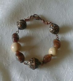 Bracciale con perle in vetro: tonde color sabbia, a goccia color marrone, perle sintetiche tonde decorate bronzo... (6,00)