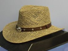 """The Siskiyou is a light and airy hat made in the USA by Silverado Hats. It is constructed of natural seagrass straw and has a 3 1/2"""" brim and 4"""" (approx.) pinch front crown. Features include a faux leather band with braiding and conchos and a mo"""