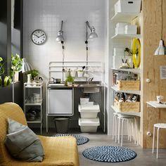 Маленькая белая мини-кухня с переносной индукционной варочной поверхностью и маленьким холодильником. На фотографии вместе с тележкой и настенными полками для дополнительного хранения