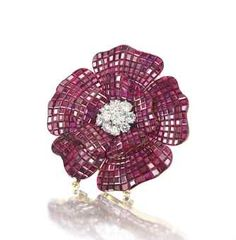 A FINE MYSTERY-SET RUBY AND DIAMOND BROOCH, BY VAN CLEEF & ARPELS Of flowerhead design, the brilliant-cut diamond cluster centre, to a mystery-set ruby double petal surround, circa 1980, 5.6cm, with French assay marks for platinum and gold, in Van Cleef & Arpels suede case Signed Van Cleef & Arpels, no.M40311
