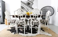 Erin gates Interiors - black & white cowhide rug layered over jute rug, white shield back chairs with zebra cushions and wood dining table.