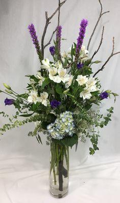 purple liatris, white alstroemeria, purple lisianthius, blue hydrangeas, baby blue eucalyptus, seeded eucalyptus, and branches in a tall cylinder vase