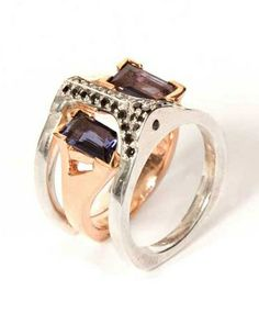"""Inspired by the concept of navigation, the center u-shaped ring is rose gold with v-shaped prongs holding a Vikings Compass Gemstone, also know as iolite. This gemstone, used by the vikings to navigate, is polarized and is fabled to have shown the direction of the north star. The surrounding bridge ring, or """"fathom"""" meaning embracing arms, does just this to the inner ring. Limited edition of only eleven made, in the USA. By BLISS LAU."""