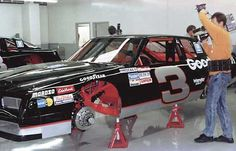 A first generation, silver numbered GM Goodwrench Chevrolet Monte Carlo SS on jack stands, and on display at the RCR museum