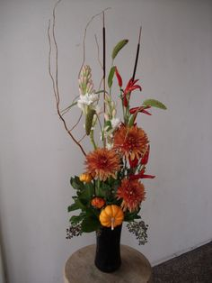 Orange , white and red fall color flower arrangement for wedding and events.