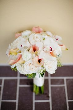 Mostly white wedding bouquet with slight accents.