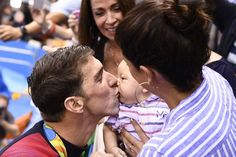 USA's Michael Phelps, left, kisses his son Boomer next to his partner Nicole…