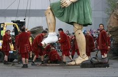 "A giant puppet is prepared to roam the streets of Liverpool, England, April 22, as part of French street theater company Royal De Luxe's performance of ""Sea Odyssey."" In the three-day production, three giant puppets are brought to life to tell a love story inspired by the sinking of the Titanic."