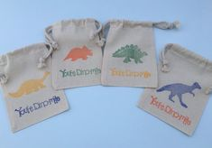 Hand stamped drawstring muslin bags with 4 different colorful dinosaur designs and Youre Dinomite slogan, perfect favor bags for your dinosaur