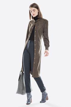 Koszula z delikatnej tkaniny imitującej zamsz, rozcięcia po bokach, zapinanie na zatrzaski, dodatkowy pasek do przewiązania w talii. Modelka ma 178 cm wzrostu i prezentuje rozmiar 36.