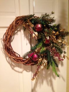 Wreath I made for JTs house. Super fun and easy to make. Bought bouquets of greenery, the gold decor and ornaments at hobby lobby. I cut the bouquets apart and stuck the stems in at an angle until it looked the way I wanted and hot glued in place. I pinned ornaments on with wire ornament hangers. And it's hanging by the wooden wreath frame on a clear door hook.