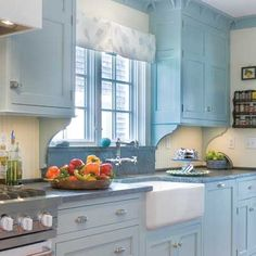 In an effort to maintain the period look of this 1932 Cape Cod remodel, close attention was paid to details like the intricate bracketed molding and drawer pulls. It is the robin's-egg-blue cabinets, though, that really grab attention and create the illusion of space in the small room.