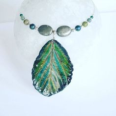 Necklace made with a porcelain leaf and genuine turquoise beads + silver + pyrite, one of a kind, Handmade in Switzerland.   www.ilemas.ch/en/