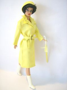 When the heavens open up, Barbie is prepared, she wears her sunny yellow raincoat and matching sou'wester style hat made in cotton . The coat has false pocket flaps, collar and yoke detail, and cinches at the waist with a brass buckled belt. A white handled yellow (un-openeing) umbrella matches, and has a cute tassle detail. Barbie sploshes in the puddles with her white boots.