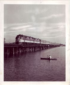1959: Illinois Central's southbound City of New Orleans passenger train crossing Lake Ponchatoula, near the end of its 921-mile trip from Chicago, as a local fisherman looks on. The cypress swamp of Lake Ponchatoula was a significant barrier to land transportation between New Orleans and the north until Illinois Central predecessor New Orleans, Jackson & Great Northern Railroad completed its line in 1854.