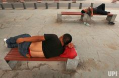 Chinese men take an afternoon nap under an expressway with city temperatures hitting close to 100F in Beijing on July 12, 2017. China is…