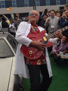 It's Doc Brown, wearing Google Glass, arriving in his DeLorean Time Machine, and holding Marty McFly's Gibson guitar. Nerd excitement... overload.