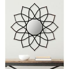 Add modern flower power to any room. The coffee and bronze finish on this contemporary mirror highlights the organic geometry of its artfully hand-wrought iron frame.