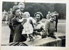 Photograph of taken in a park setting of Princess Elizabeth (b. 1926), later Queen Elizabeth II who stands behind a wall on which walks the infant Princess Anne (b. 1950), later The Princess Royal. Standing behind Princess Elizabeth is King George VI (1895-1952). On the right is Princess Margaret (1930-2002) and Queen Elizabeth (1900-2002), later Queen Elizabeth the Queen Mother.