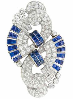 An Art Deco Platinum, White Gold, Diamond and Sapphire Double Clip-Brooch 1935. The stylised scroll motif set with 108 round, 4 single-cut and 18 baguette diamonds, approximately 10.80 cts., embellished by two pairs of intersecting bands of 20 square-cut sapphires and tipped by pairs of 24 square-cut sapphires, altogether approximately 8.00 cts., circa 1935.