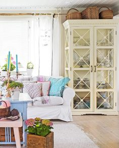 Suuri vitriinikaappi astiastoineen on olohuoneen komistus. Sen seuraksi sopivat pajukorit, pehmeä sohva ja iloinen sohvapöytäryhmä. Katso inspiroiva kuva!