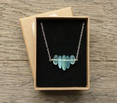 This dainty sea glass necklace is full of the sparkle of foamy waves as they crash on a sandy bay.  The cultured sea glass is made from recycled glass that has been tumbled for a week with diamond sand to look as if it has just been washed ashore after hundreds of years of weathering by the sea, sand, and surf. Each piece of glass is about 1 - 1.5 cm long. The width of the bar is approximately one inch.  Delicate yet strong, the chain is designed to add a wisp of a shimmer to your neckline…
