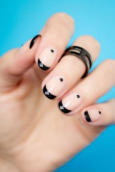 Black tip French manicure with added black dots near base.
