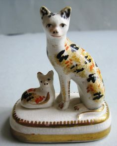 """Seated Cat with Laying Kitten. A Calico Coloured Cat and Kitten on a Base. Circa 1840. 3""""."""