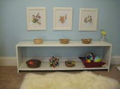 A simple low shelf with a handful of accessible toys & low art work; rotate toys as necessary.