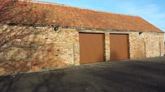 Two Walnut coloured roller garage doors installed at a barn near Sleaford