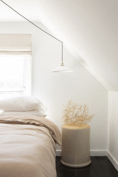 """In another instance of found utility, the bedside table on one side of the bed is from a surprising source: """"It's a massive, oversize crockpot that we found in my husband's grandmother's garage—we turned it upside down to use it as a nightstand,"""" Przystup says. A tumbleweed serves as a sculptural moment on top. #remodelista"""