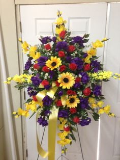 Silk Funeral Spray using yellow gladiolus, yellow sunflower, purple roses, red rose buds, and white filler flowers with yellow ribbon streamers. January 2016