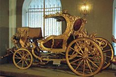 This is the splendid two-seated summer carriage in the form of an Italian gondola that was executed in England in the 1770s. It was presented to Empress Catherine the Great from Count Orlov. Decor of the carriage reflects the influence of two styles - rococo and classicism. It is adorned with magnificent wood carving of laurel and oak leaves, flower garlands, banner and trophies and covered with a thin layer of gold which gives the impression of carved metal.