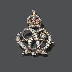 An early 20th century enamel and diamond brooch, circa 1905 The scrolling monogram, set throughout with single and old brilliant-cut diamonds, to a crown surmount with red enamel detail and demantoid garnet and single-cut diamond highlights, one garnet deficient, length 3.0cm., fitted case