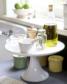 Clear up the clutter and make the most of your countertops by using a cake stand to hold frequently used seasonings.....USE OTHER PLACES, TOO!  Bathroom, dresser, desk....I've been doing this for years with cologne & perfume on my dresser...so pretty with a white linen & lace doily setting under the perfume bottles!
