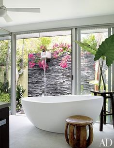 A slate-walled waterfall shower by landscape designer Raymond Jungles is just outside the master bath at author Judy Blume's Key West, Florida, home. | archdigest.com