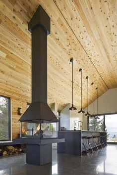 Chic barn style home in Quebec The mirror effect of radiant concrete floor accentuates the fluidity of the space and reflects the abundant natural light onto cedar walls and ceiling. Under an impressive cathedral ceiling, a fireplace is conveniently placed in the center of the open plan to unify the various activities of reading, cooking, eating and relaxing. The ambiance of the space plunges us into a comfort similar to that of old wooden homes.