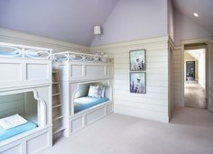 Fun girls' bunk room features vaulted ceilings painted lavender, Benjamin Moore Spring Violet, over ivory horizontal groove paneling framing wall-to-wall built in bunk beds dressed in turquoise blankets and white and lavender shams accented with wainscoting trim flanking built-in bunk bed ladder.