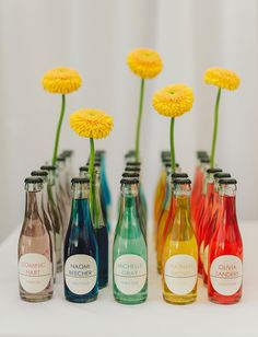 Rainbow colorful soda bottles used as guest escort cards for table assignments. Very cute. Would be great for an art deco wedding too.