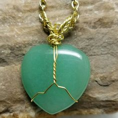 Gold wrapped aventurine heart pendant on gold colored chain necklace.