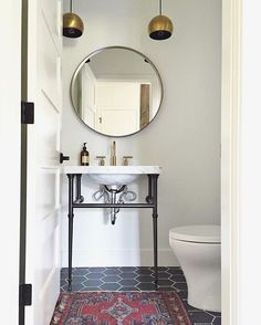 Bathroom with black hexagons and @schoolhouseelec pendants. Designed by Kirsten Grove