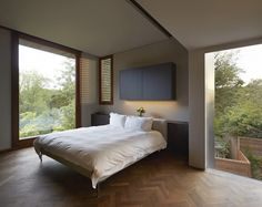 This bedroom offers a quiet space to relax and enjoy nature through the large windows. The minimalist decor allows for small details to stand out - like the beautiful herringbone wood floor.
