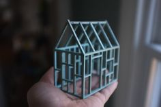 A freestanding, 3D line drawing, the exposed framework of this miniature wooden house is stained a pale blue to highlight the geometry of the structure