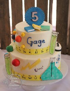 Science themed cake Cakes are covered in white buttercream Decorations are made from fondant.