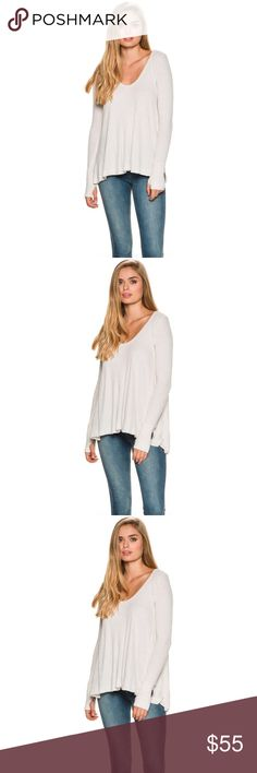 """NWT Free People Ivory Malibu Thermal The Ivory Malibu Thermal by Free People is the comfiest, coziest tee + we guarantee you'll want to wear it every day this fall. Wide scooped neckline. Long sleeves. Wide cuffs with thumb-holes. Long tunic length. High to low hem with side splits. Flowy fit. Thermal texture. Pair it with denim skinnies + boots for a no-fail outfit. 95% Rayon; 5% SpandexSize & Fit Guide Model is wearing size Small. Model's height: 5'10.5"""" Model's chest: 33.5 inches. Model's…"""
