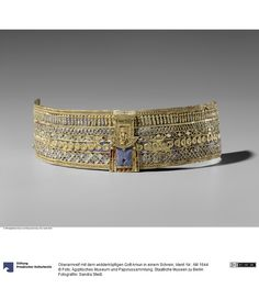 Upper arm bracelet with the ram-headed god Amun in a shrine (Sudan / Nubia / Butana (area))Made of Gold; Glass flow (inlays), dark blue, light blue, red (multi-colored) 3 x 20 cm Ancient Egyptian Jewelry, Dark Blue, Light Blue, Arm Bracelets, Gold Glass, African Art, Flow, Red, Accessories